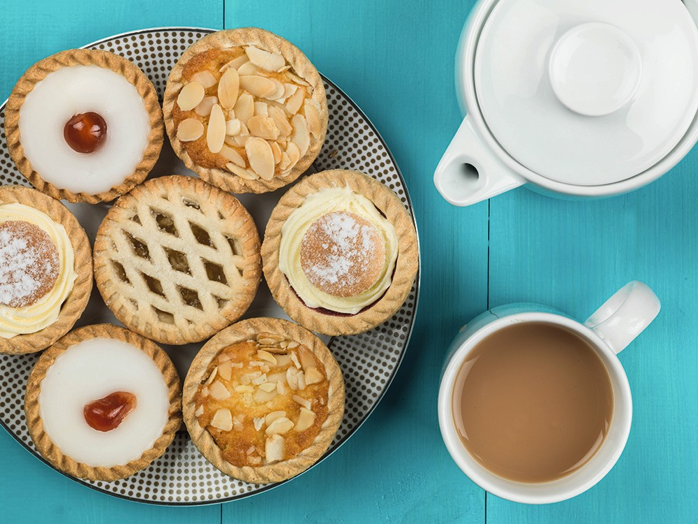 Plate of Assorted Individual Cakes or Tarts With a Pot of Tea Against a Blue Background