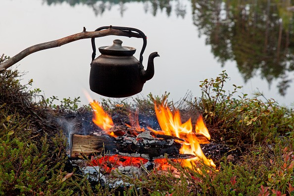 Blackened tin kettle boiling water over flames from campfire during hike along lake. (Photo by: Arterra/UIG via Getty Images)