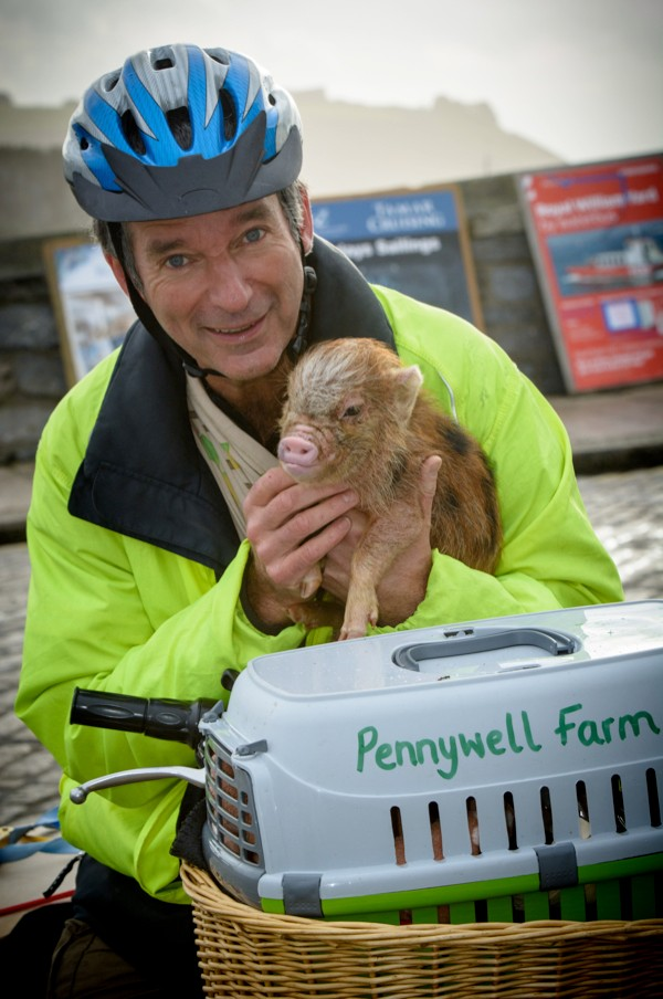 Friday 20 December 2013 Picture by Sean Hernon Tony Hawks cycles with miniature pig called Titch from Pennywell Farm Titch gets to the Mayflower steps Plymouth