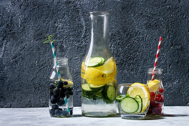 Citrus cucumber berries blueberry and raspberry sassy sassi water for detox in glass bottles on gray texture background. Clean eating, healthy lifestyle concept, sunlight. (Photo by: Natasha Breen/REDA&CO/UIG via Getty Images)