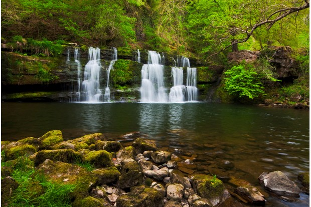 Long exposure image of a waterfall in spring surrounded by lush green foliage. Photo taken at Sgwd y Pannwr, Brecon Beacons national park, Wales.
