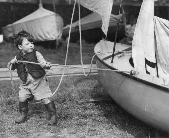 17th April 1952: 2-year-old Simon Maddison, complete with life-jacket and gum boots, helps his father prepare their Firefly Class yacht 'Transient' for the forthcoming yacht race on the Thames. (Photo by Harry Todd/Fox Photos/Getty Images)