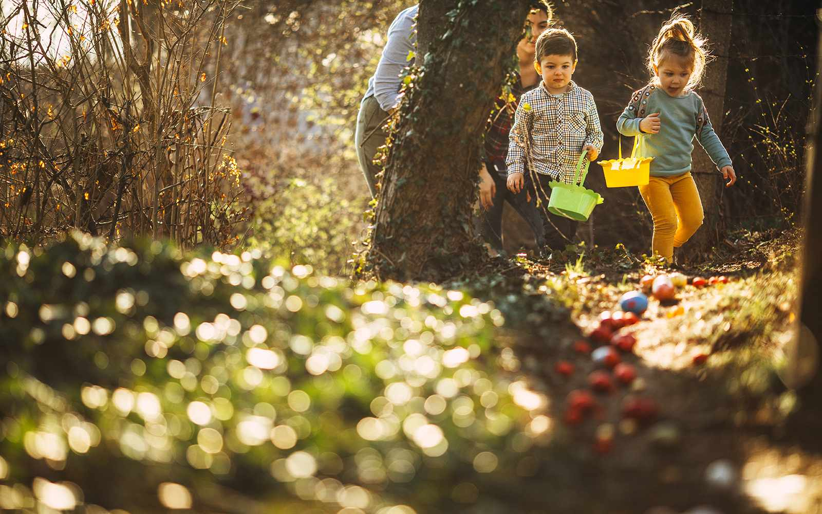 Cute little kids and their moms during Easter egg hunt