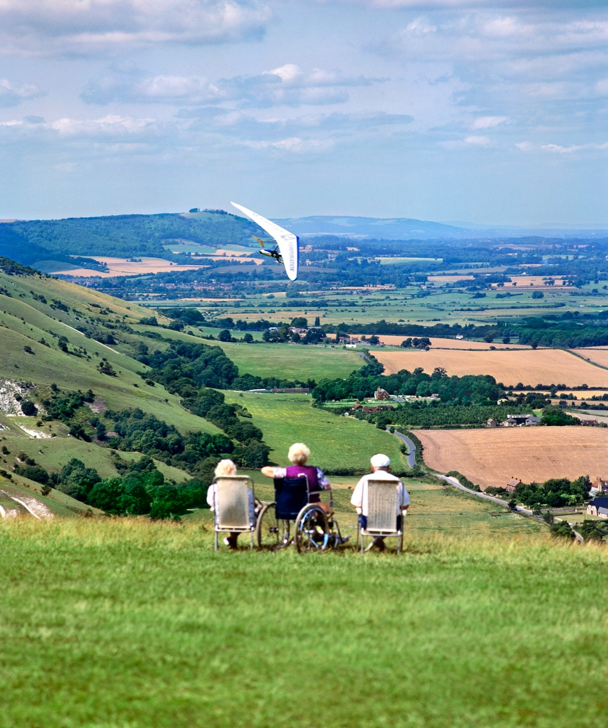 A wheelchair user and friends admire the view and a hang glider from a hilltop on the South Downs at Devils Dyke near Brighton