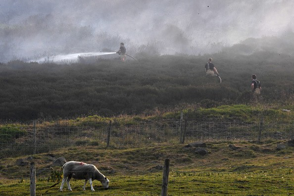 STALYBRIDGE, ENGLAND - JUNE 27: Fire officers continue to fight a large wildfire on the moors above Stalybridge, Greater Manchester on June 27, 2018 in Stalybridge, England.  Firefighters have declared a 'major incident' as they battle the huge moorland fire which measures 6km. (Photo by Anthony Devlin/Getty Images)