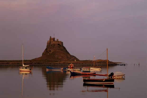 View of boats at moorings in the dusk at Lindisfarne Castle, Northumberland.