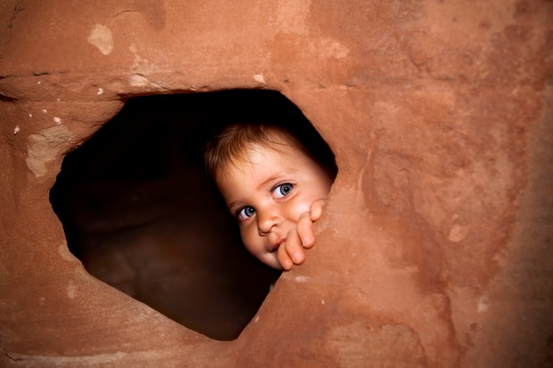 A child peeking out of a hole in the rock, part of a family vacation at Capitol Reefs National Park