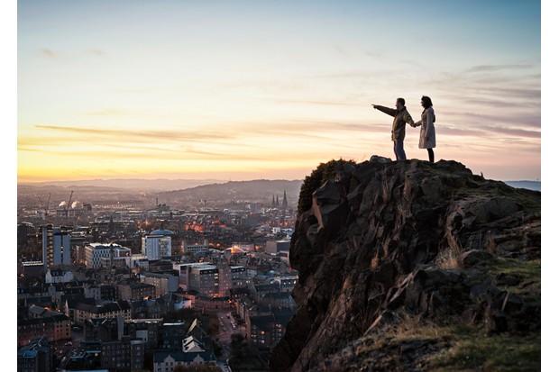 A couple looking out over the City of Edinburgh from Salisbury Crags in Holyrood Park.