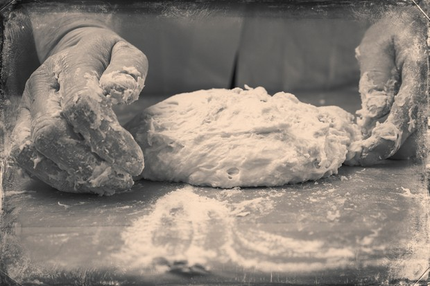 Closeup photo of baker making yeast dough for bread. black and white retro styled imagery
