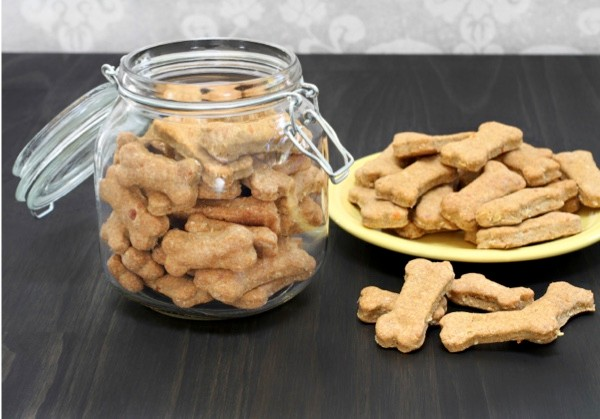 Homemade, healthy dog bones in a canister and on a wooden counter.  A healthy, safe, homemade treat for a dog.