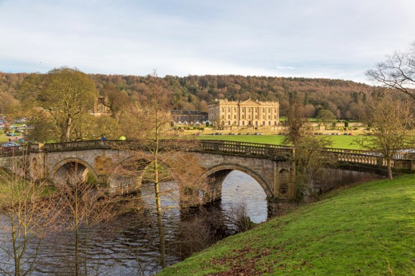 Bakewell, UK - April 2, 2015: Chatsworth House Front View took from the Garden in Bright Blue Sky. This Old European Style House is famous place for tourism and located in Peak District, Derbyshire.