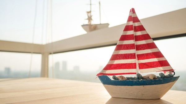 Sailboat model on wooden table.