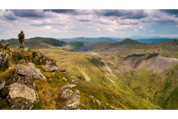 Climbing high: a lone hiker looks east from the rocky crest of Cnicht, one of 93 summits over 2,000ft (610m) in Snowdonia National Park ©Alamy