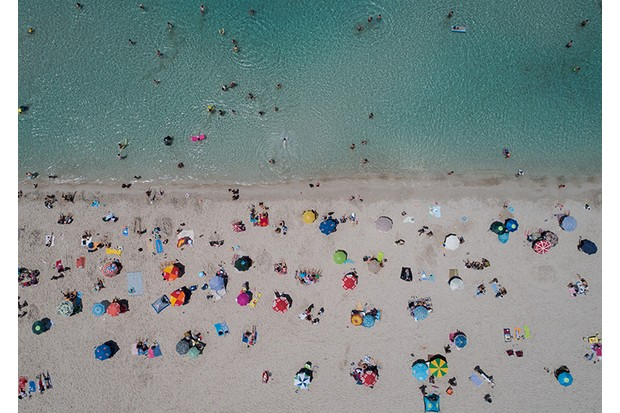 IZMIR, TURKEY - JUNE 16: A drone photo shows the aerial view of a beach as people sunbathe under colourful parasols and swim on a summer day at Cesme district, during the Eid al-Fitr in Izmir, Turkey on June 16, 2018. (Photo by Mahmut Serdar Alakus/Anadolu Agency/Getty Images)
