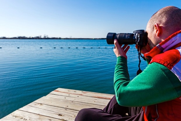 Photographer is take a photo sitting on the platform, shoots a lake