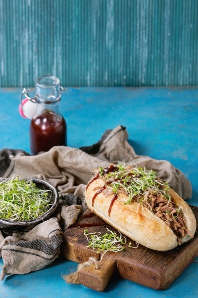 Pulled pork sandwich with meat, green sprouts and bbq ketchup, served on wood cutting board with small bottle of tomato sauce and bowl of greens over bright blue wooden background. (Photo by: Natasha Breen/REDA&CO/UIG via Getty Images)