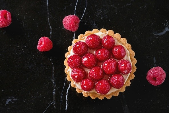 Tartlet with custard and fresh glazed raspberries, served on black marble surface. Top view. (Photo by: Natasha Breen/REDA&CO/UIG via Getty Images)