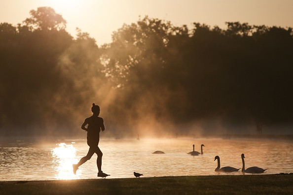 A jogger runs past the Round Pond as the sun rises at Kensington Gardens in London on August 31, 2017 / AFP PHOTO / Daniel LEAL-OLIVAS (Photo credit should read DANIEL LEAL-OLIVAS/AFP/Getty Images)