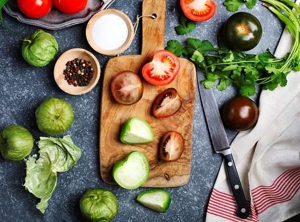 Chopped tomatoes and knife on cutting board, fresh vegetables on the table, top view. (Photo by: Anjelika Gretskaia/REDA&CO/UIG via Getty Images)