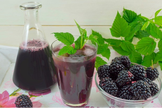 Blackberry juice in glass and bottle with fresh blackberries served
