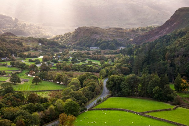A road cuts through green fields and woodland in a valley near Beddgelert in Snowdonia, North Wales. Late afternoon sunbeams on the hills behind.