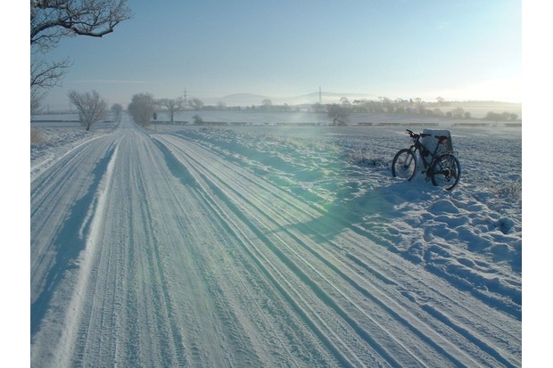 """Darlington, on a snowy day, cycle propped on a milestone on National Route 1"