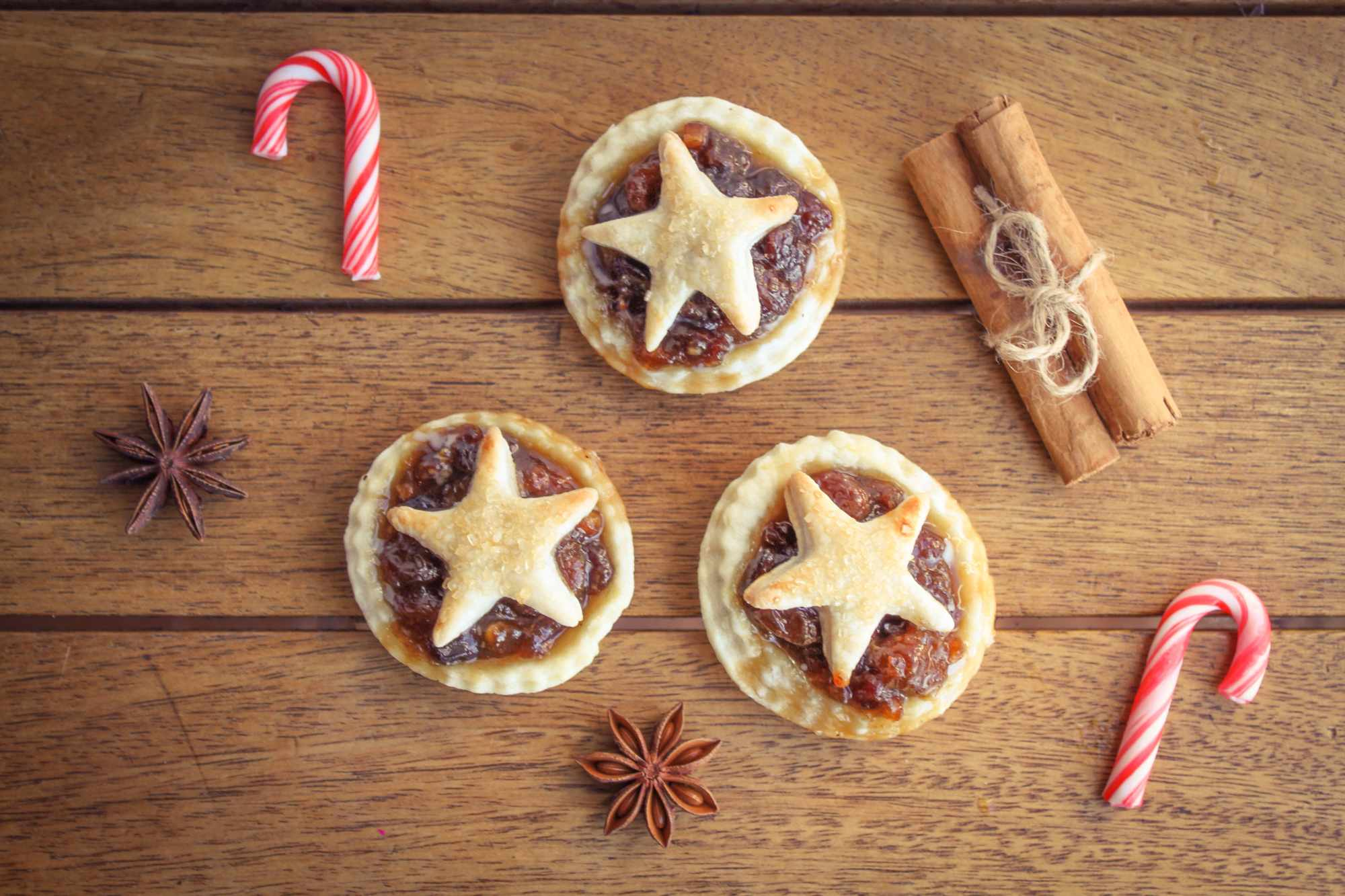 Traditional homemade mince pies with candy canes and star anis and cinnamon sticks (Getty)