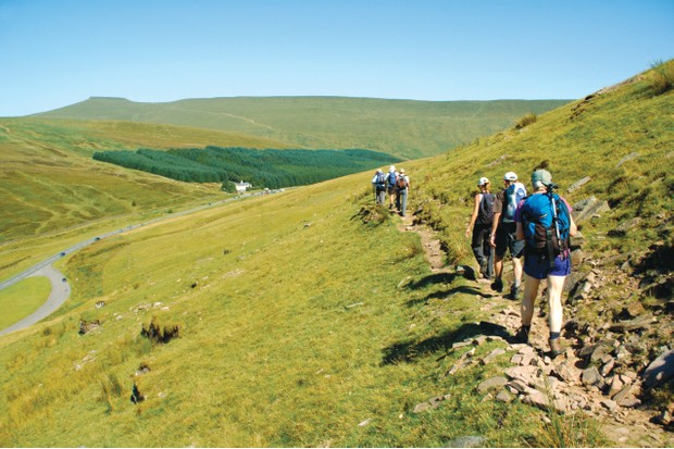 Guided walking group on hillside track heading toward Storey Arms in the Brecon Beacons National Park ©Getty