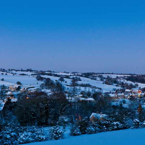 Idyllic winter village church cottages snow covered landscape Cotswolds UK