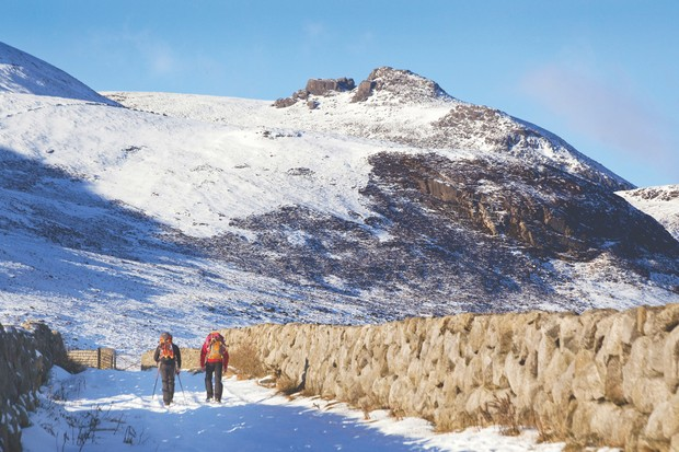 Hikers stride towards Slieve Binnian, with the North Tor towering above. The word 'slieve' derives from the Irish word 'sliabh', meaning 'mountain' ©Getty
