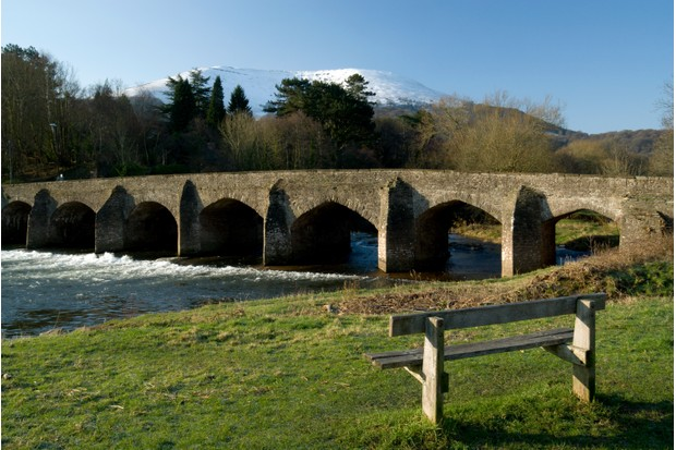 River with stone bridge and mountain view