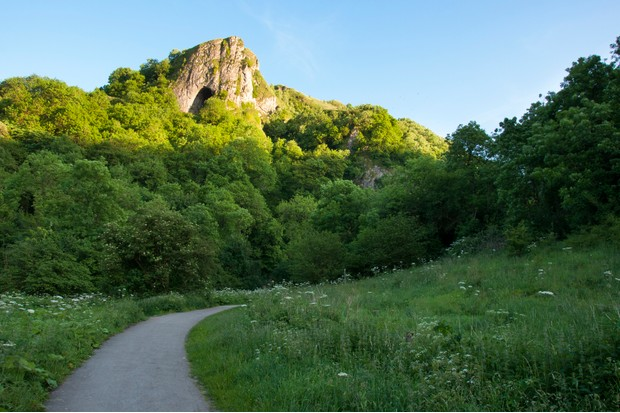Looking up at Thors cave from the path that follows the Manifold valley in Staffordshire.Taken one evening in summer with sunlight catching the rocky summit of the hill.