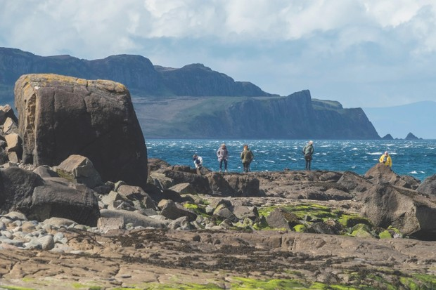 Tourists looking for fossilised dinosaur footprints on Staffin Beach, An Corran, Isle of Skye, Scotland