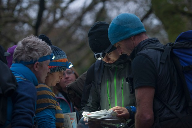 Group of people studying map, orienteering