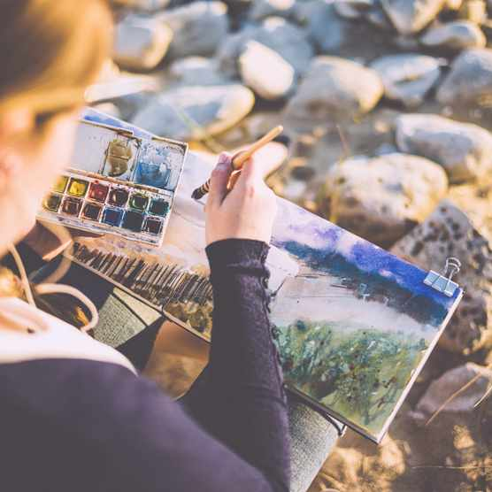 Woman painting watercolour outdoors