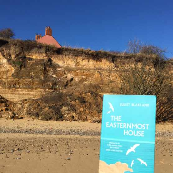 Book on beach with house and crumbling cliff