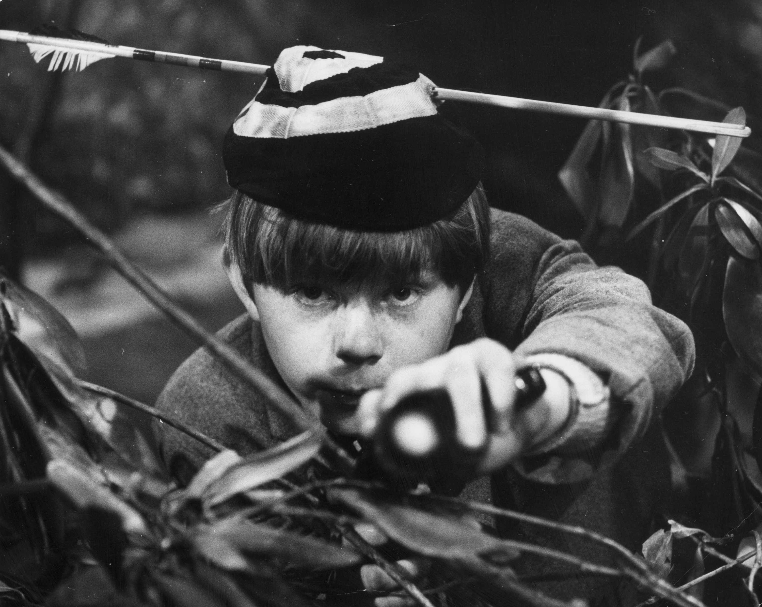 Boy peering through plant