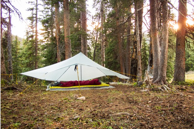 A backpacking camp scene with a tarp tent and sleeping bag in the trees. Photo taken during a backpacking trip into the Weminuche Wilderness around the Rio Grand Pyramid peak, Colorado.