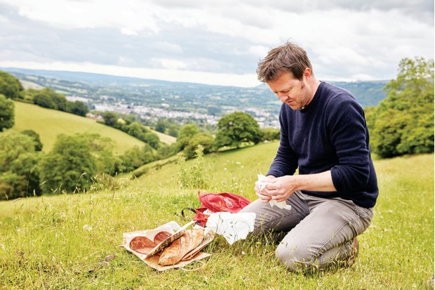 Fergus Collins enjoys a picnic in an Abergavenny field with a view of the town behind him