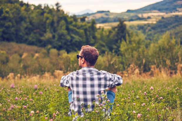 Man taking a break in nature and looking at the distant landscape.