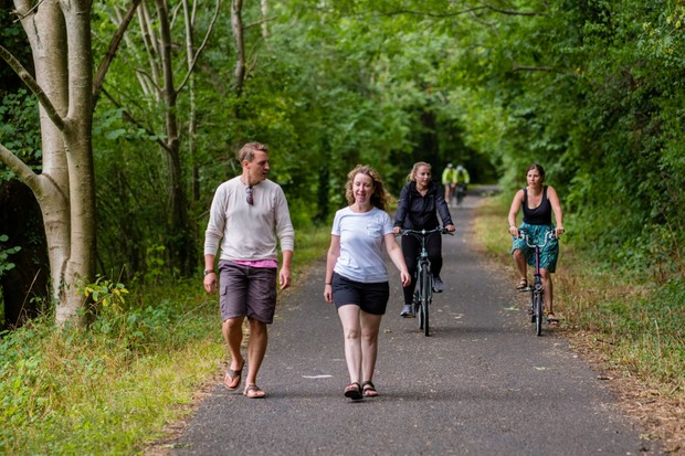 Walkers and cyclists enjoying traffic-free path through woodland (National Route 4, Bristol and Bath Railway Path, Severn and Thames).