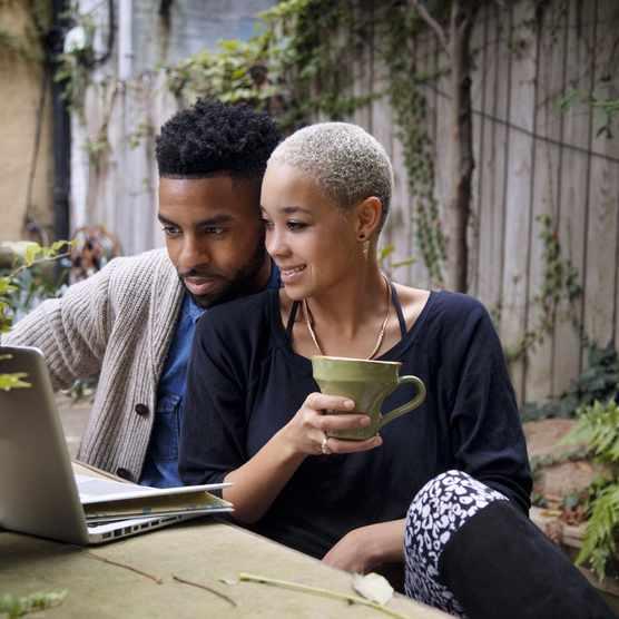 Couple using a laptop in their garden