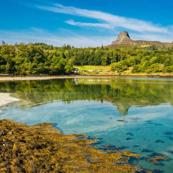 Isle of Eigg, Small Isles, Scotland. Beautiful bay in Summer with blue sky and An Sgurr reflected in the clear blue waters