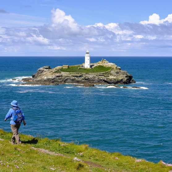 Woman hikes on coastal route at Godrevy Point, Godrevy Lighthouse on Godrevy Island, near Gwithian, Cornwall, England, Great Britain