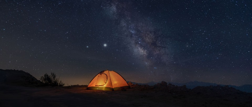 Lit-up tent under a starry sky at night.
