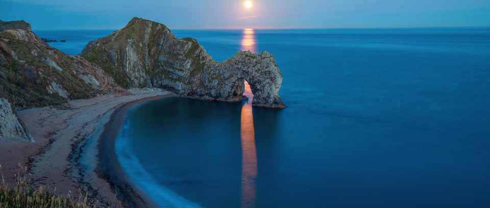The setting sun on the horizon of the ocean casts a perfect line of gold through the hole in the rock at Durdle Door in Dorset
