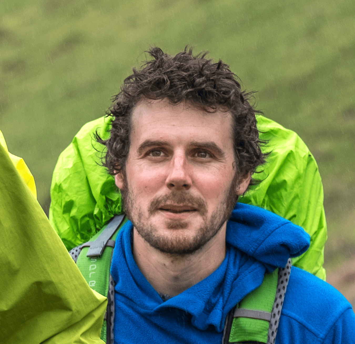 Daniel Graham of BBC Countryfile Magazine on a hike with wet hair and blue coat and hills in background