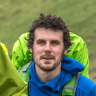 Daniel Graham of COuntryfile magazine on a hike with wet hair and blue coat and hills in background