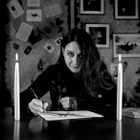 Karen Ruffles in black and white sitting at table drawing with two long candles in the foreground