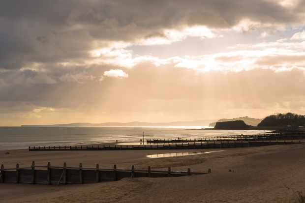 Sun breaking through the clouds at Dawlish Warren in winter